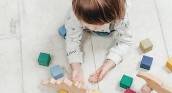 Imagen de niño jugando con bloques boca abajo.