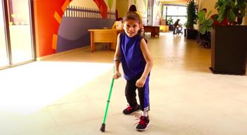 Fotografía de niño sonriente caminando con muletas en los pasillos de TeletonUSA