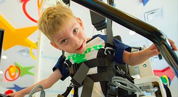 Foto de un niño en el CRIT utilizando el Lokomat, un dispositivo robótico para la rehabilitación de la marcha